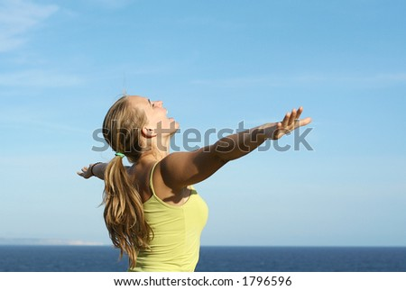 Young girl arms out stretched to the sky. Might be good to advertise travel. - stock photo