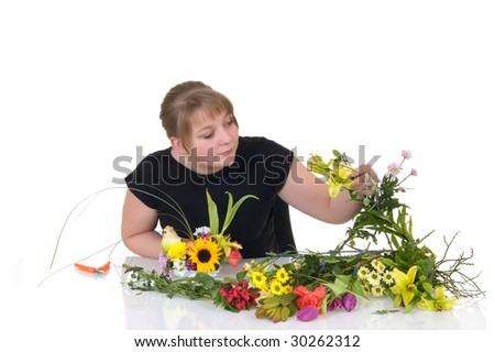Young girl arranging flowers on reflective surface, white background, studio shot - stock photo