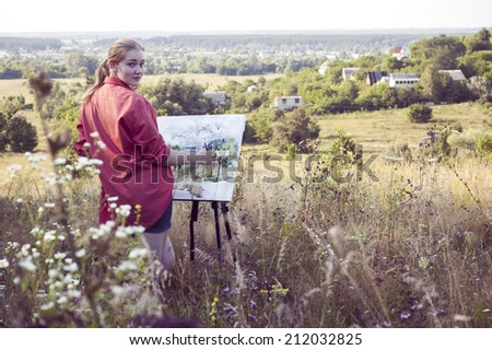 Young girl-artist is painting with watercolor on the plein Air - stock photo