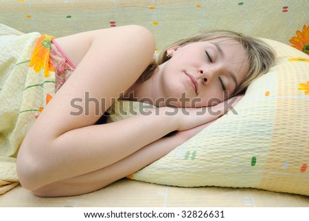 Young girl asleep in her bed - stock photo