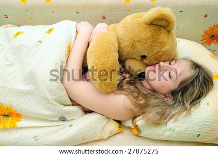 Young girl asleep in her bed with a teddy bear - stock photo