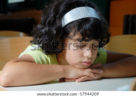 Young Girl Asleep on Book at Desk in School - stock photo