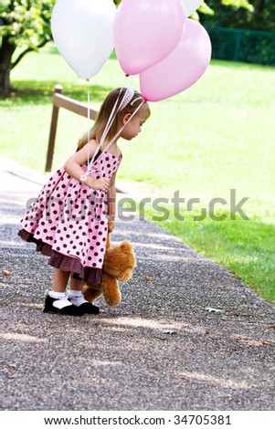 Young girl at a park with pink and white balloons and a little brown teddy bear toy.