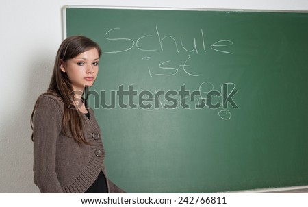 Young girl at blackboard with text school sucks - stock photo