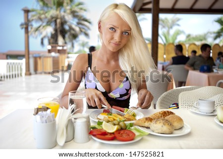 young girl at breakfast on the restaurant terrace