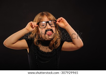 Young girl at Halloween party with spectacles and fake mustache