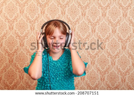 Young girl at home listening to music on a pair of vintage 1970s wired headphones looking down happy holding the earphones - stock photo