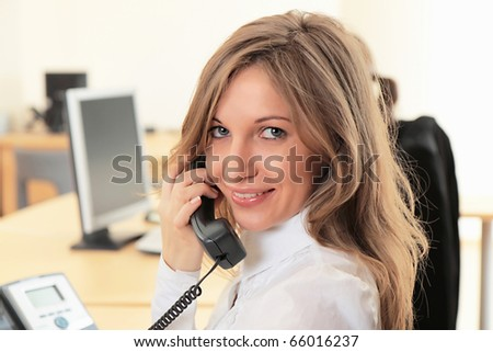 Young girl at office on the workplace makes call.