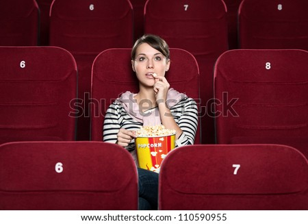Young girl at the cinema watching a movie - stock photo