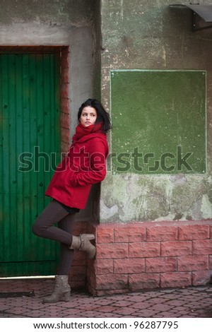 Young girl at the green door - stock photo