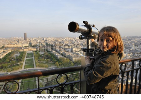 Young girl at the top of Eiffel Tower, Paris, France, Europe - with Montparnasse Tower and Champs de Mars in the background - stock photo