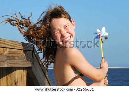 Young girl at windy beach having fun with pinwheel - stock photo