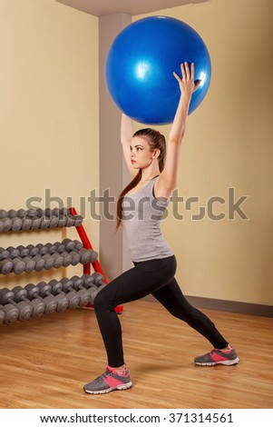 Young girl athlete squats with fitball. Training in the sport club. Fitness.