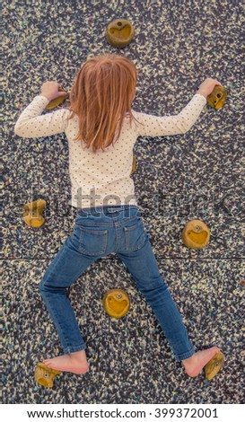 Young Girl Attempting An Inside Climbing Wall Without Ropes - stock photo