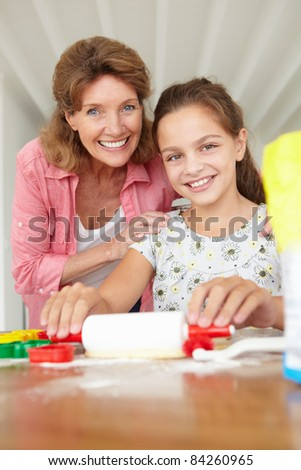 Young girl baking with grandmother - stock photo