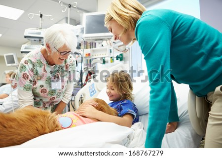 Young Girl Being Visited In Hospital By Therapy Dog - stock photo