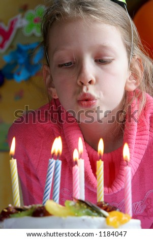 Young girl blowing  birthday candles - stock photo