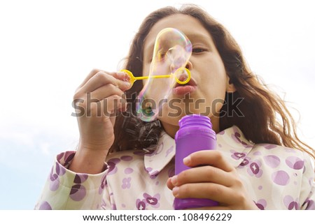 Young girl blowing bubbles against the sky. - stock photo