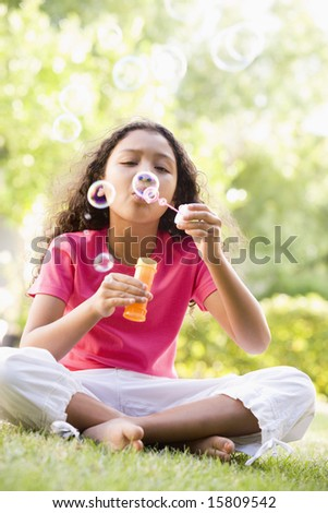 Young girl blowing bubbles outdoors - stock photo