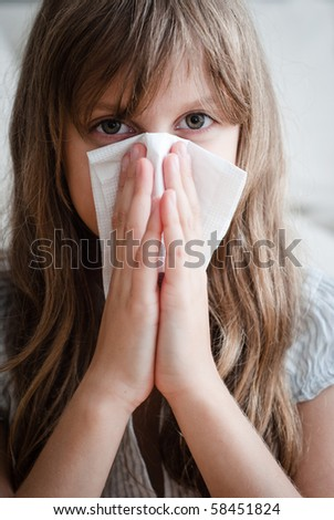 young girl blowing her nose