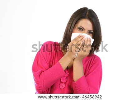 Young girl blowing her nose at tissue - stock photo