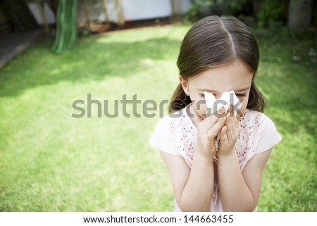 Young girl blowing nose with tissue paper in backyard - stock photo