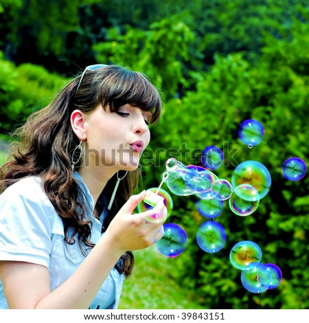 Young girl blowing soap bubbles in summer green park