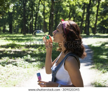 Young girl blowing soap bubbles outdoors - stock photo