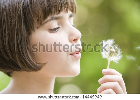 young girl blowing the seeds from a dandelion