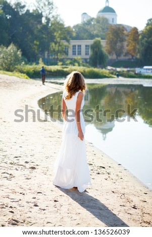 Young girl bride in a white dress on the sunny coast of the river. Outdoor - stock photo
