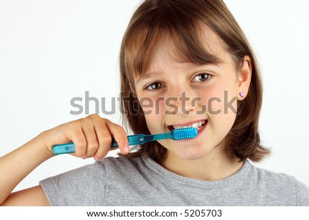 Young girl brushing her teeth against white background