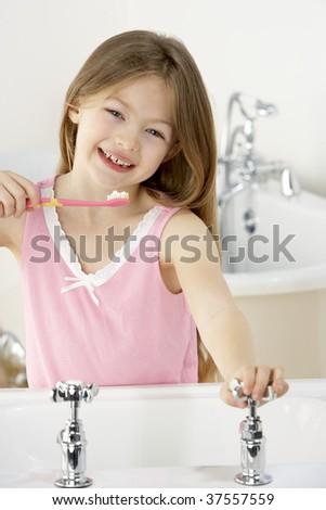 Young Girl Brushing Teeth at Sink - stock photo