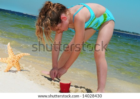 Young Girl Building Sand Castle Next to Starfish