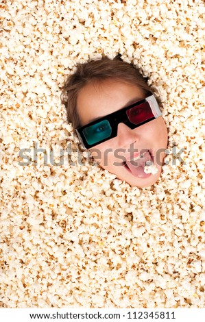 young girl buried in popcorn wearing 3d glasses