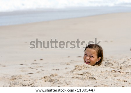 Young girl buried in the sand smiling at camera. Shot with shallow DOF for plenty of copy space - stock photo