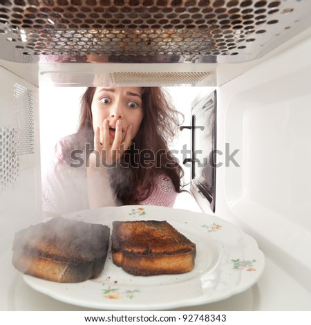Young girl burned toasts in a microwave - stock photo