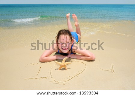 Young girl by I Love You message written in sand by starfish - stock photo
