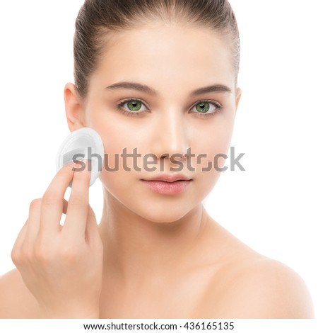 Young girl cares for face skin relaxation. Beautiful young brunette woman with clean perfect fresh skin using cotton pad. Youth and skin care concept. Isolated on a white. - stock photo
