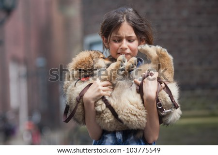 young girl carries a cute Elo puppy that is injured