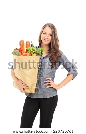 Young girl carrying a bag full of groceries isolated on white background