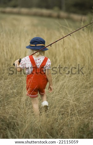 Young girl carrying a fishing pole and tackle box - stock photo