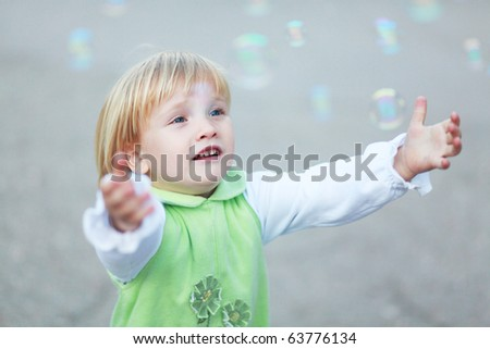 Young girl catching the soap bubbles - stock photo