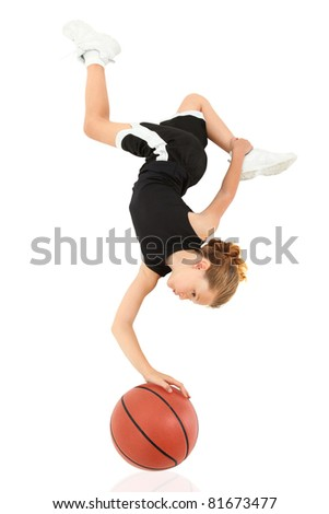 Young girl child balancing upsidedown on top of basketball in uniform over white. - stock photo
