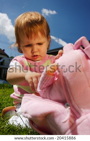 Young girl child outdoor sitting on the grass and look for her doll toy from her rucksack - stock photo