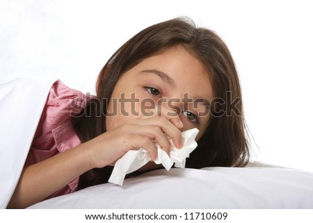 young girl / child sick in bed with a cold using tissues