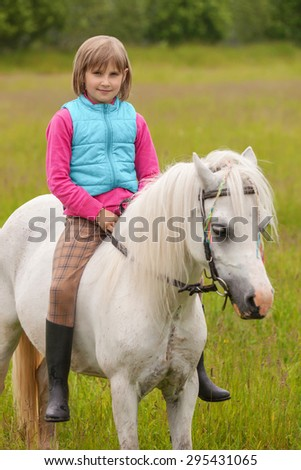 Young girl child sitting astride a white horse and smiling
