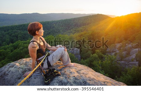 Young girl climber sitting secured with rope on big rock at mountain peak with bare foot enjoying the view on beautiful valley. Warm sunny evening in the mountains. Climbing equipment. - stock photo