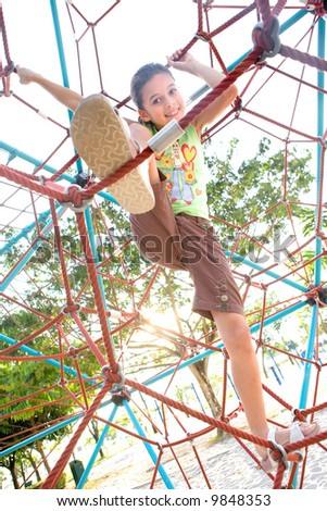 Young girl climbing giant web in playground activity - stock photo
