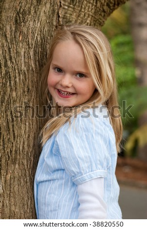 Young girl climbing tree and smiling - stock photo