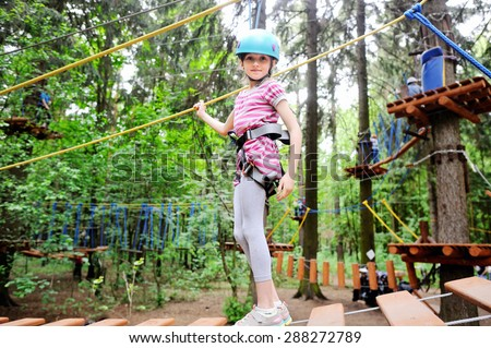 Young Girl climbing trees in the adventure park - stock photo